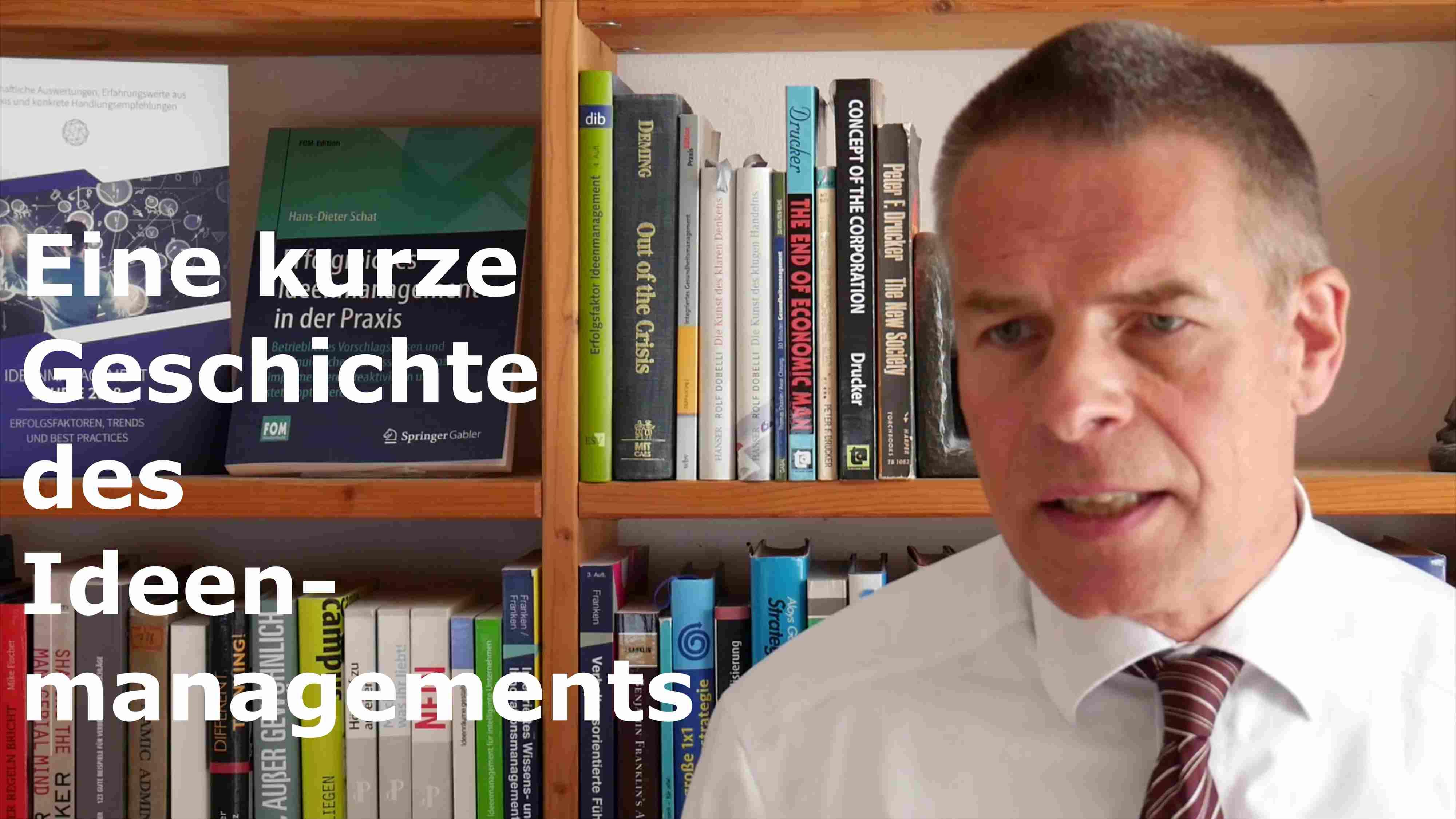 Hans-Dieter Schat vor einem Bücherregal mit der Überschrift Eine kurze Geschichte des Ideenmanagments